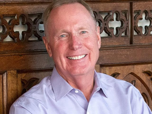 Pastor Max Lucado leaning against a carved wooden bench