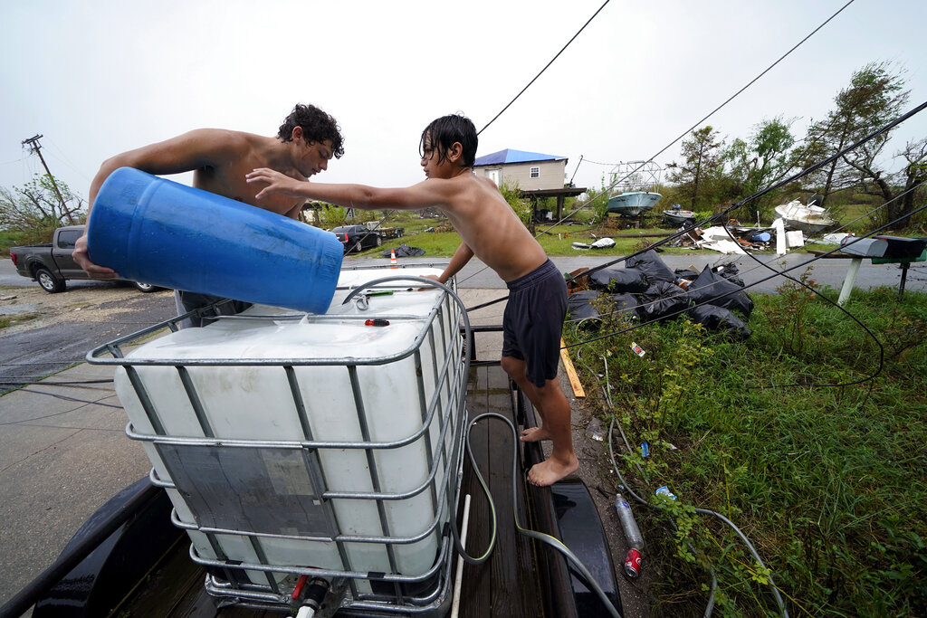 Boys pour barrels of rainwater into filter pump
