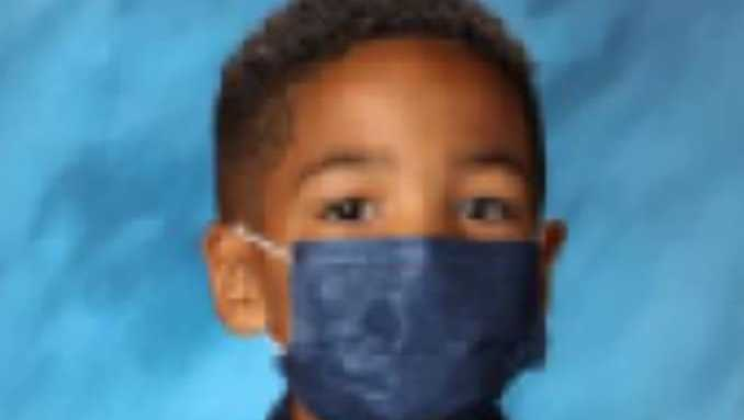 Little boy with a blue mask on for his school picture