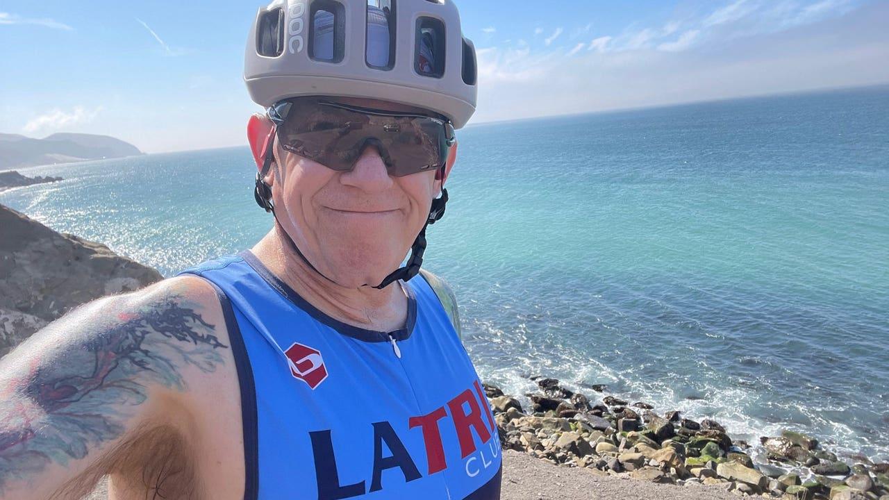 Smiling man wearing a helmet and tank top near ocean