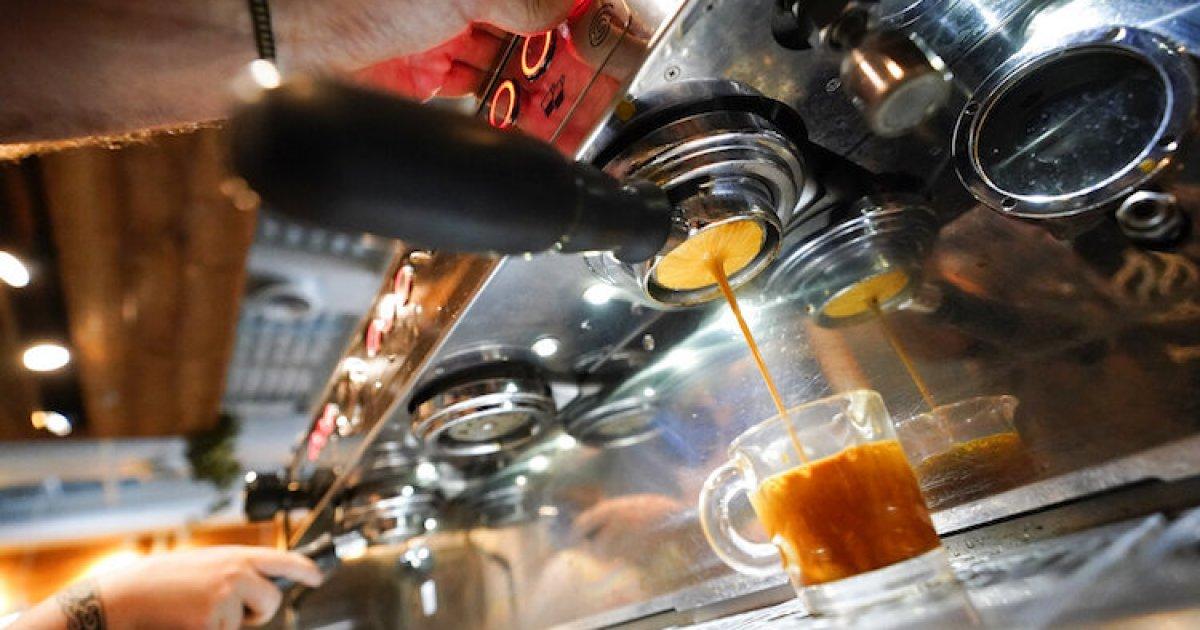 Espresso machine dispensing espresso into a small glass
