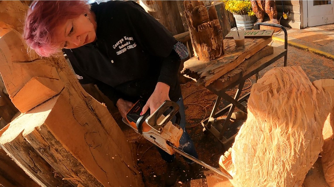 Woman carving bear using chainsaw