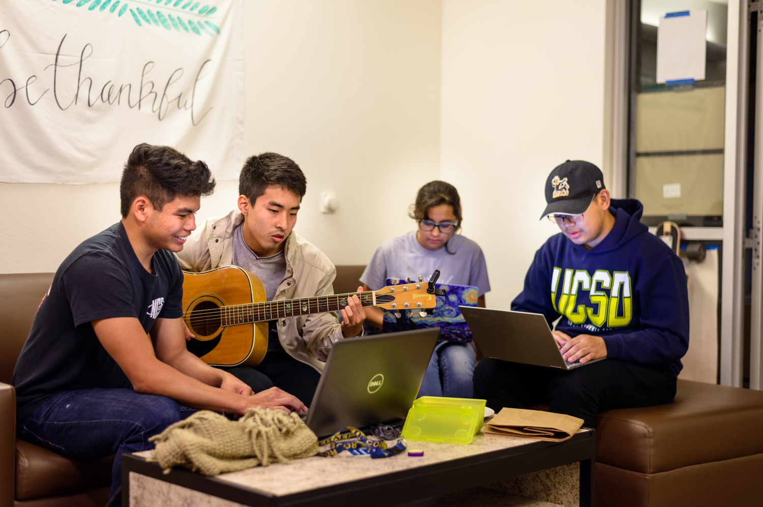 InterVarsity students sitting on couch playing guitar