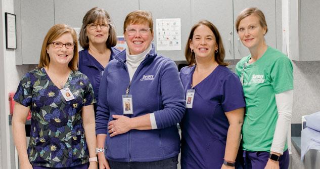 Five female medical professionals in scrubs