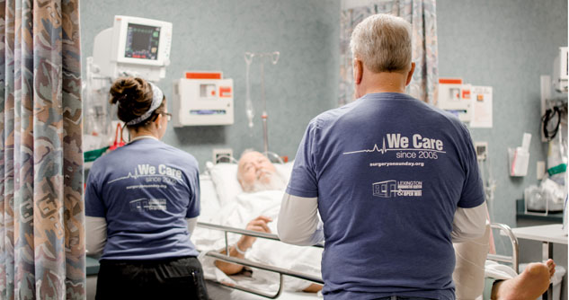 Two Surgery on Sunday volunteers wearing We Care T-shirts, attending to a patient