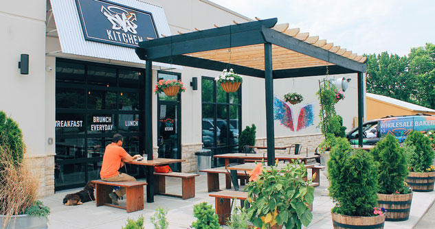 Exterior of DV8 Kitchen with benches, a man and his dog, plants