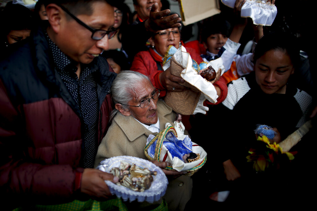 People wait their turn to have their baby Jesus dolls blessed by a priest as they leave the Three Kings Day Mass at San Francisco Church in La Paz, Bolivia. Outside the church, many parishioners went to indigenous guides to get additional blessings that come from the country