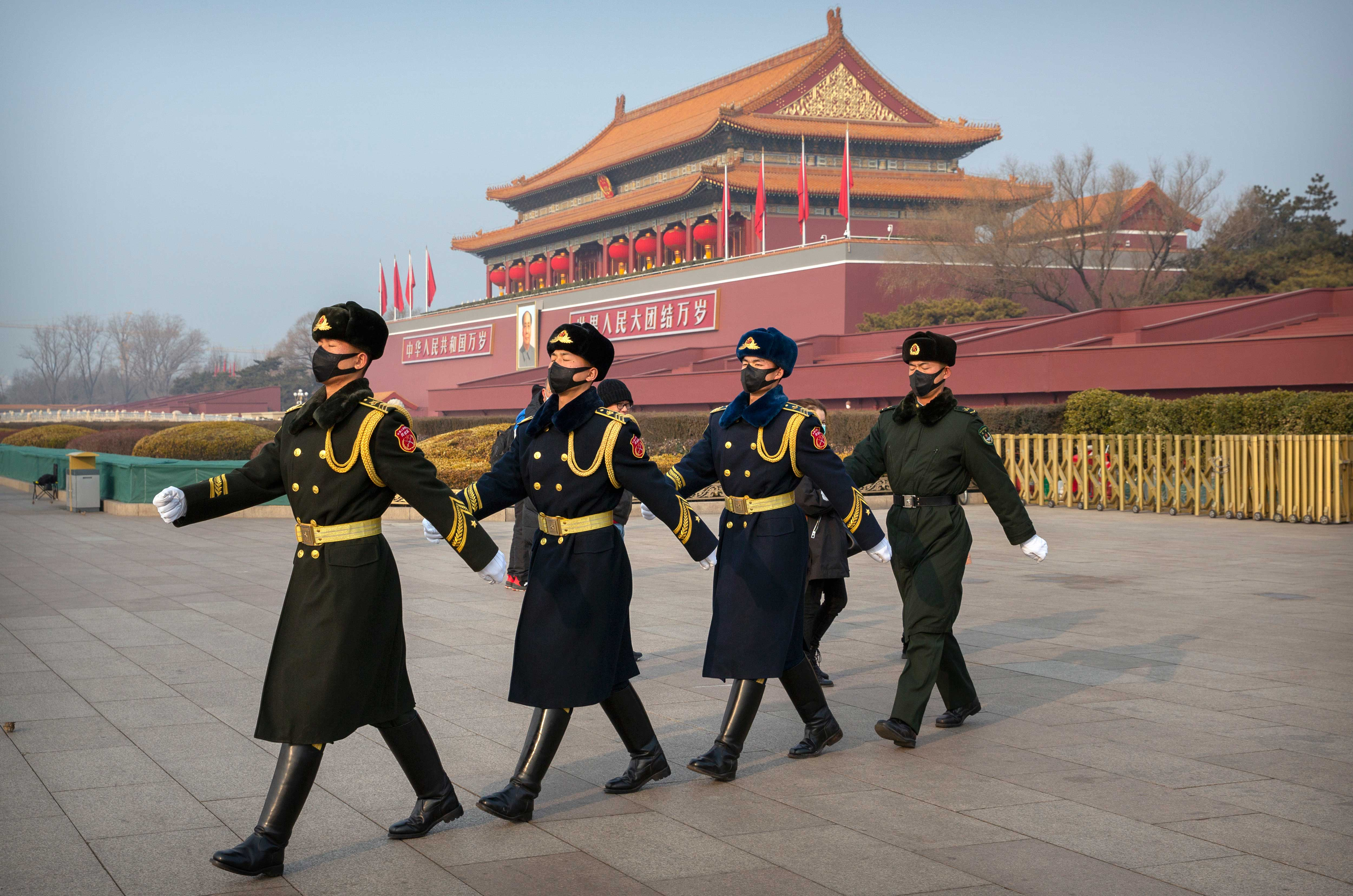Security officials march in formation near Tiananmen Gate