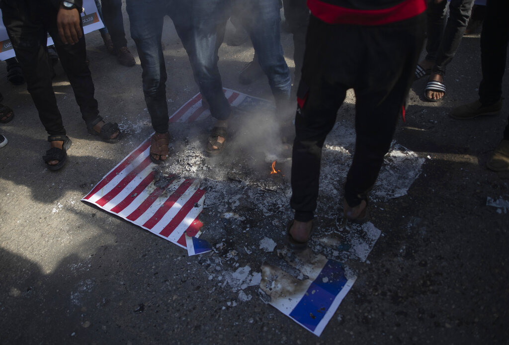 Palestinian protesters step over burning mocks of Israeli and American flags